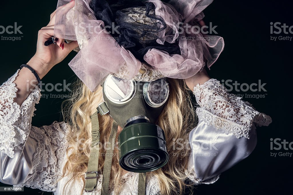 woman's wedding dress and gas mask stock photo