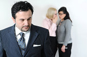 Womans whispering about businessman