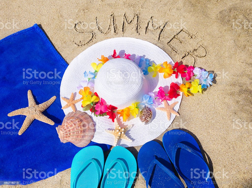 woman's white hat on the sandy beach stock photo