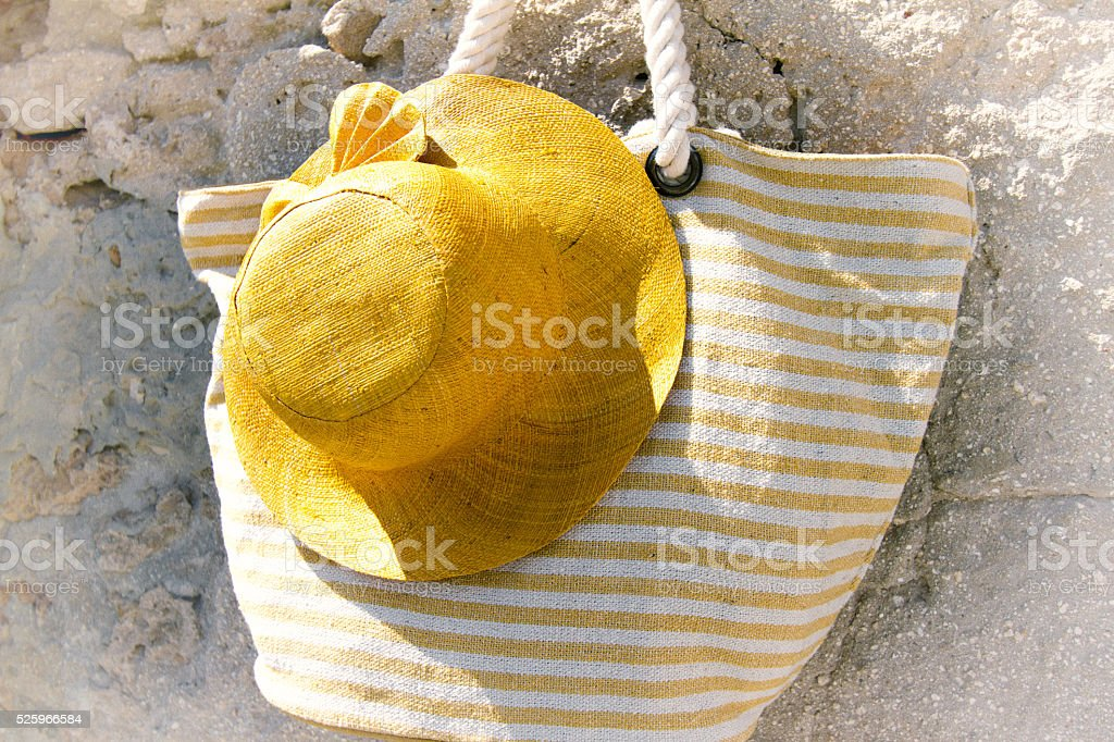 Woman's Yellow Straw Hat and Cotton Striped Bag, Stone Wall stock photo