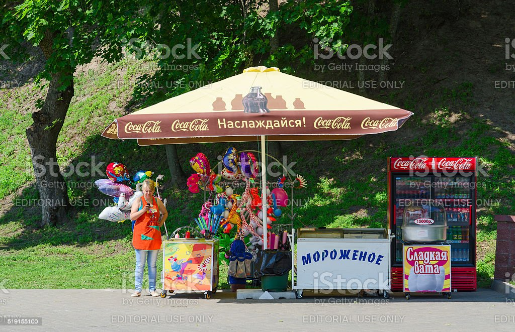 Woman-seller in park at counter with ice cream, balloons stock photo