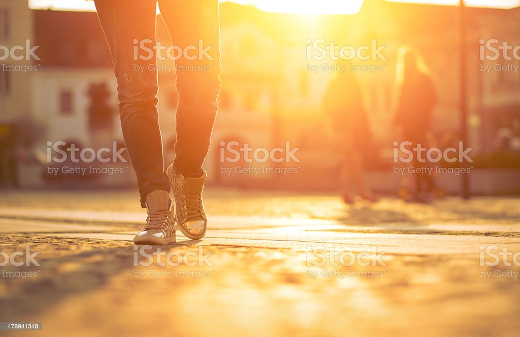 Womansfoots on the street at sunny day. stock photo