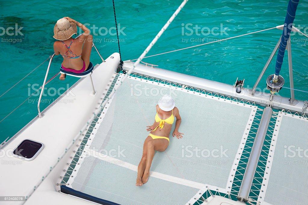 Womem relaxing on catamaran in the Caribbean stock photo