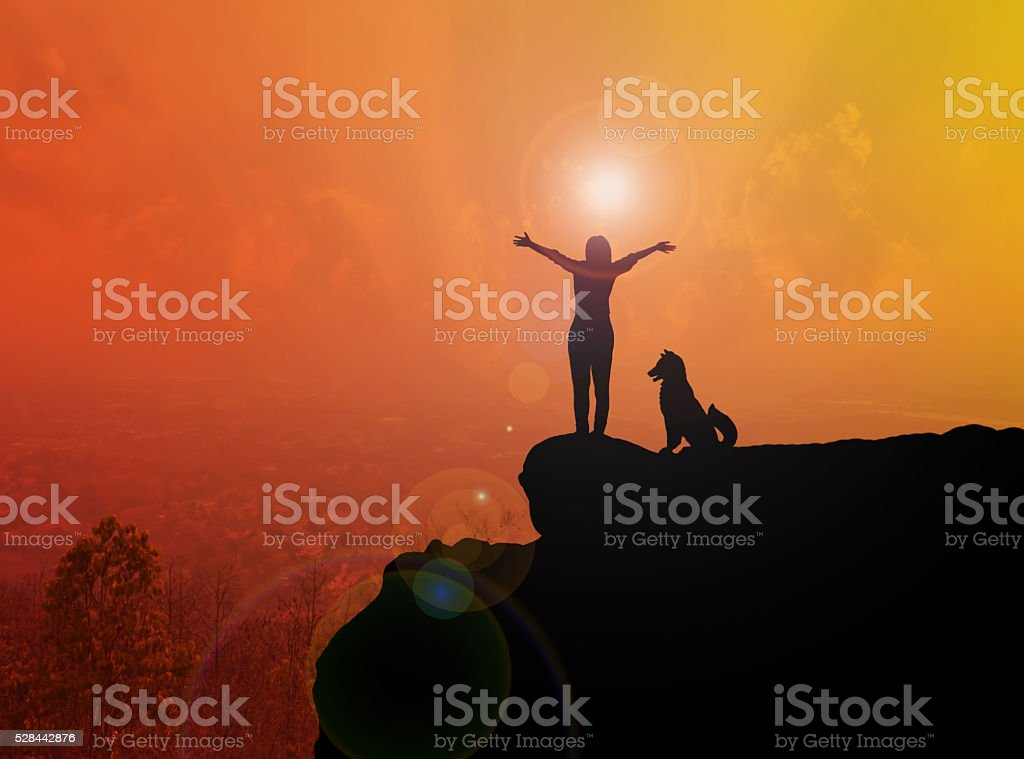 Women and dog silhouette on cliff stock photo