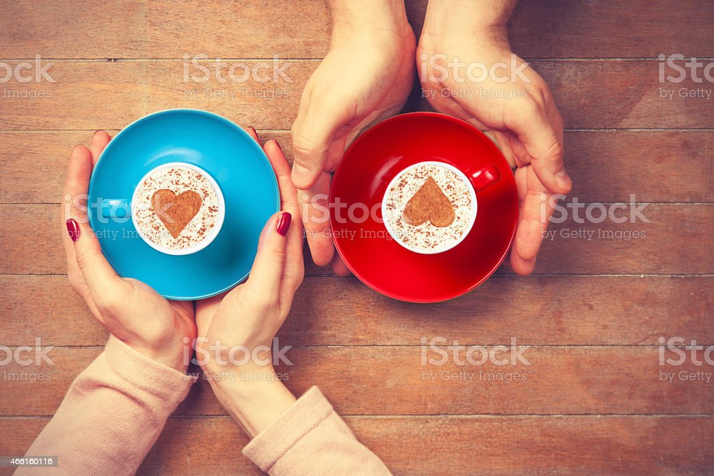 Women and man holding cups of coffee stock photo