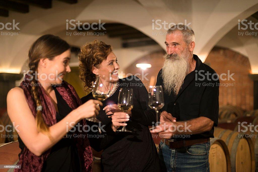 Women and Senior Man Having Fun in Wine Cellar, Europe stock photo