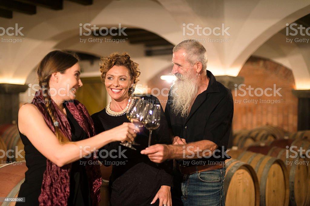 Women and Senior Man Toasting in Old Wine Cellar, Europe stock photo
