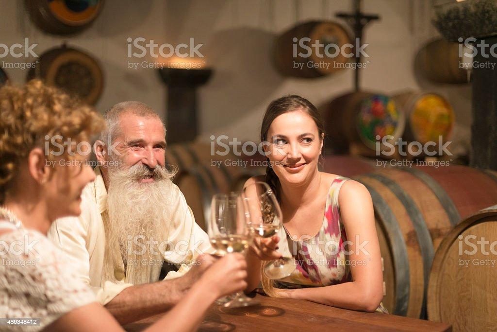 Women and Senior Man Toasting with White Wine, Cellar, Europe stock photo