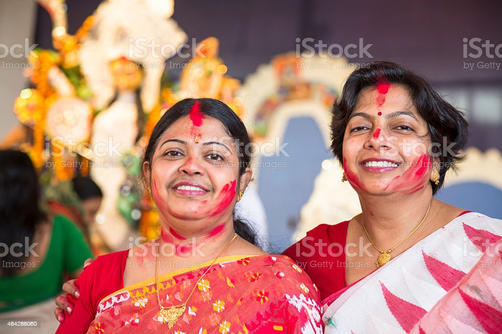 Women applying ritualistic Vermilion on each other during Durga Puja stock photo