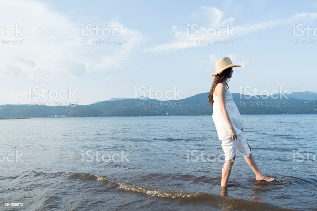 Women are quietly to the thinking in the lake. stock photo