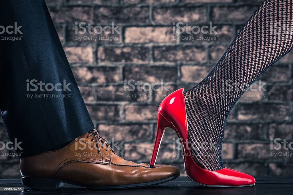 women are stepping on the shoes of the man stock photo