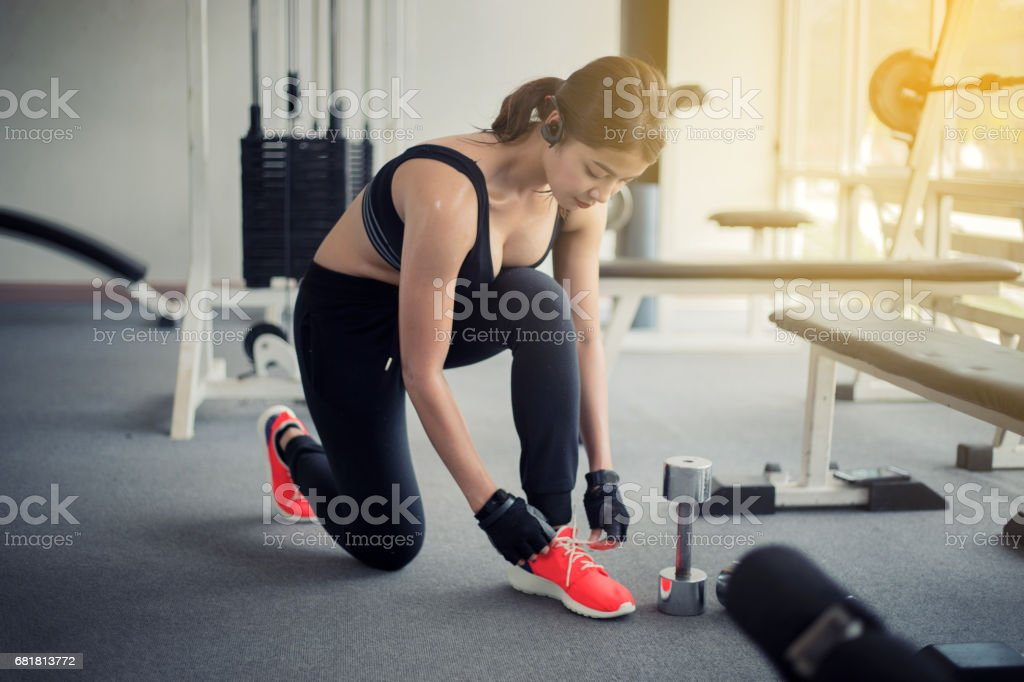 women asian tying shoe laces. fitness women getting ready for engage in the gym stock photo