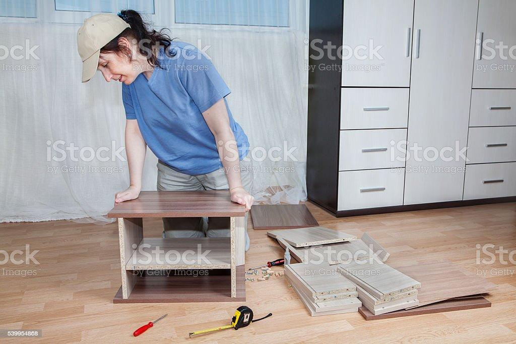 Women Assembling Flat Pack Furniture On Floor In Living Room Royalty Free Stock Photo