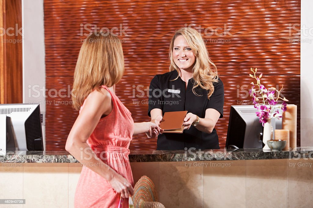 Women at hotel reception desk stock photo