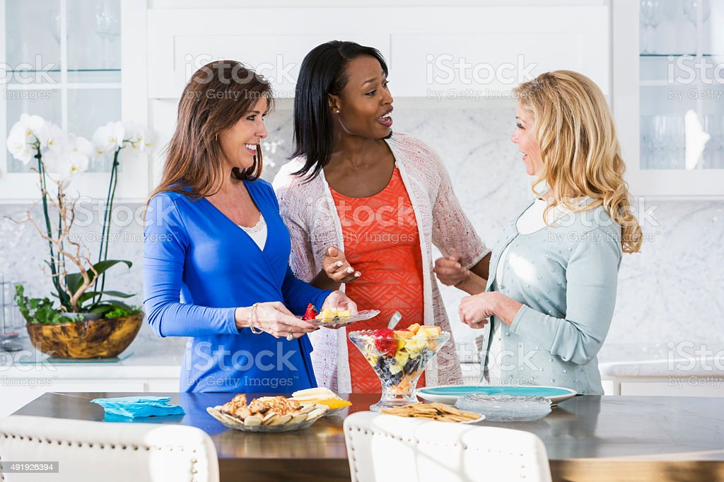 Women at luncheon having conversation in kitchen stock photo