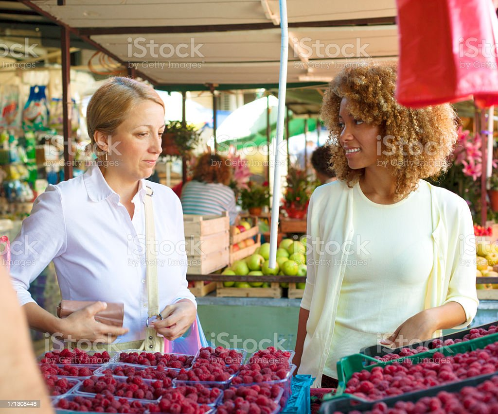 Women at market buying raspberry. royalty-free stock photo