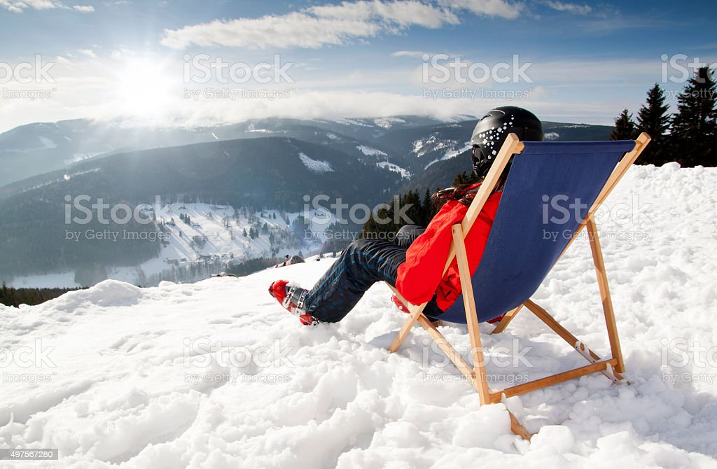 Women at mountains in winter lies on sun-lounger stock photo