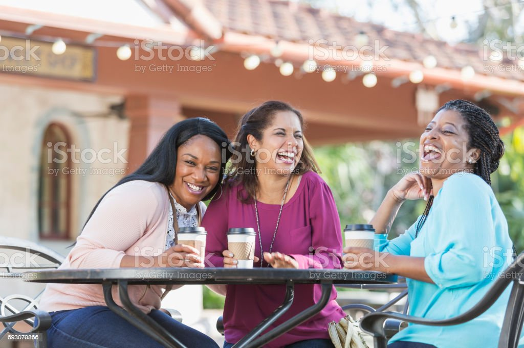 Women at sidewalk cafe drinking coffee, laughing stock photo