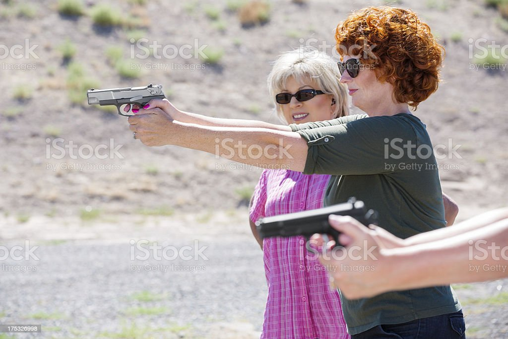 Women at the outdoor shooting range aiming guns royalty-free stock photo