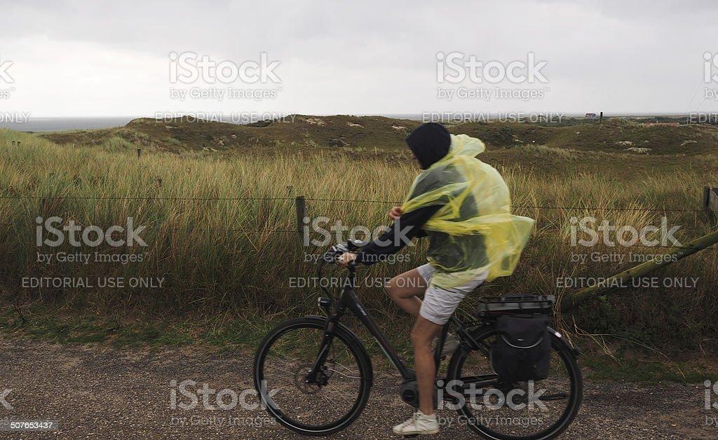 Women biking in the rain on Texel, Netherlands stock photo