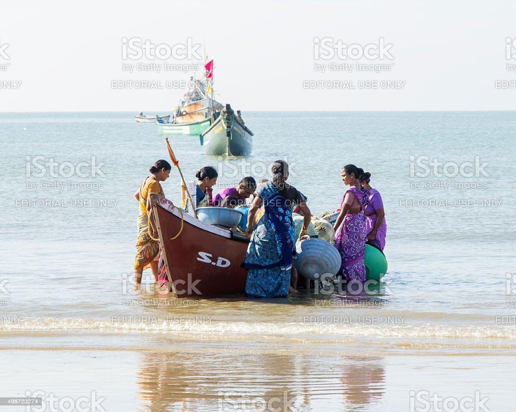 Women buying fish from boat, Murudeshwar, Karnataka, India stock photo