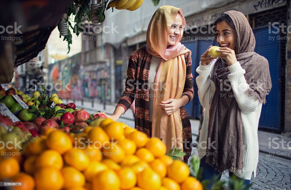 Women buying fruits from the street vendor stock photo