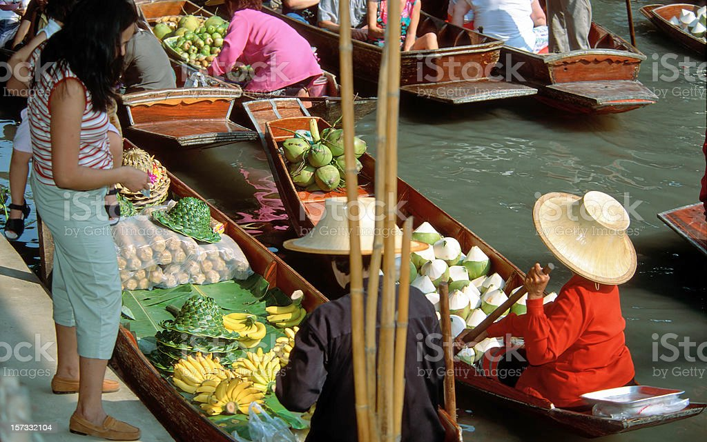 Women buying fruits on the floating market royalty-free stock photo