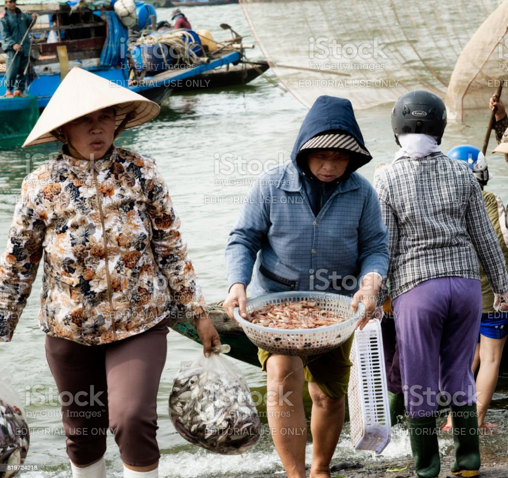 Women carrying plastic bags with fresh catch of fish and a basket with shrimps. December 26, 2013 - Da Nang, Vietnam stock photo