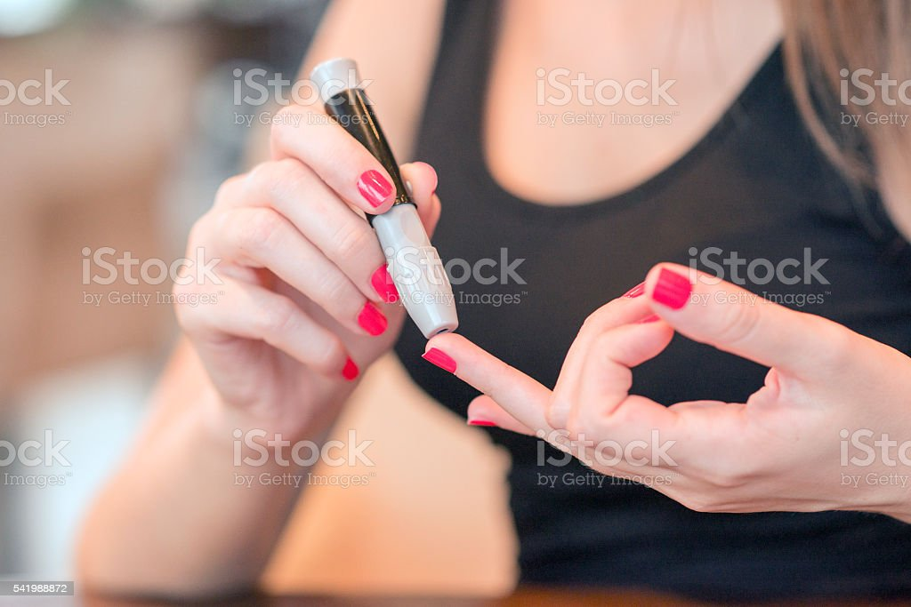 Women Checking Blood Sugar Level At Home stock photo
