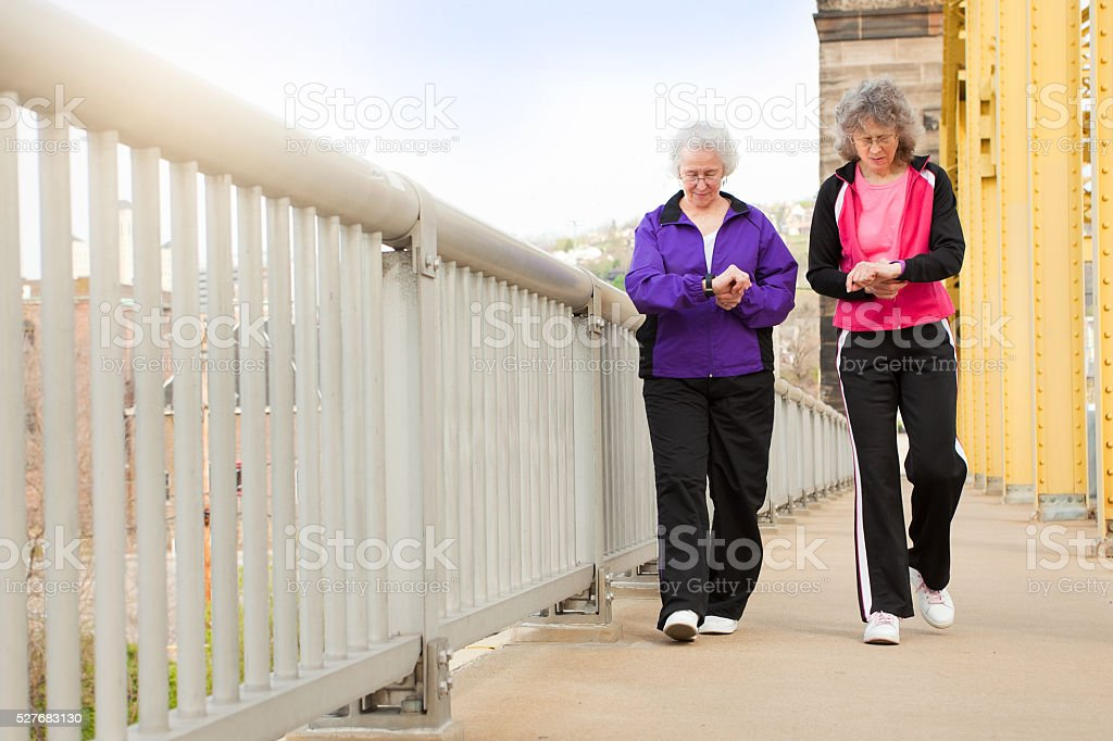 Women Checking Fitness Watches As They Walk stock photo