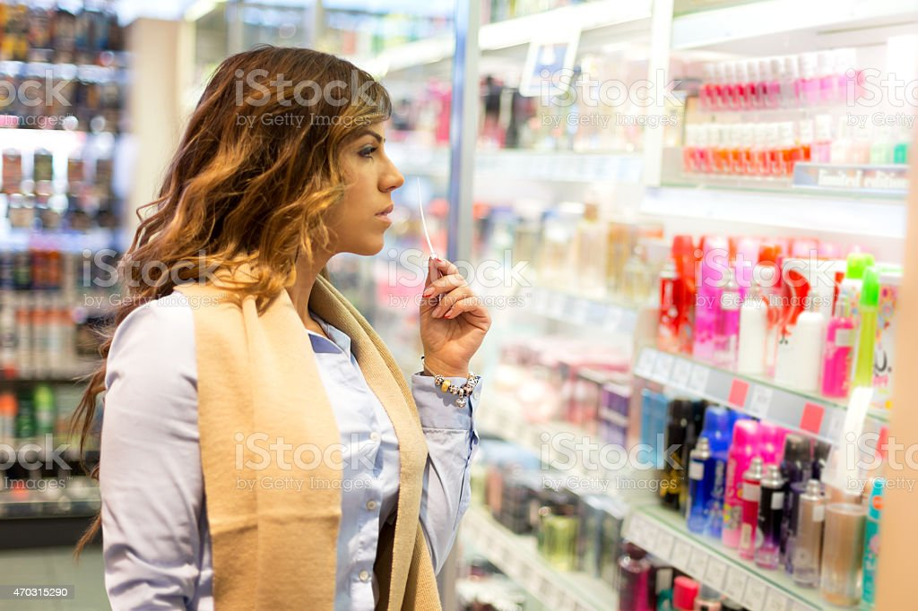 Women choosing parfume in shopping mall stock photo