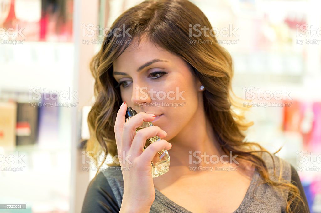 Women choosing perfect perfume in mall stock photo