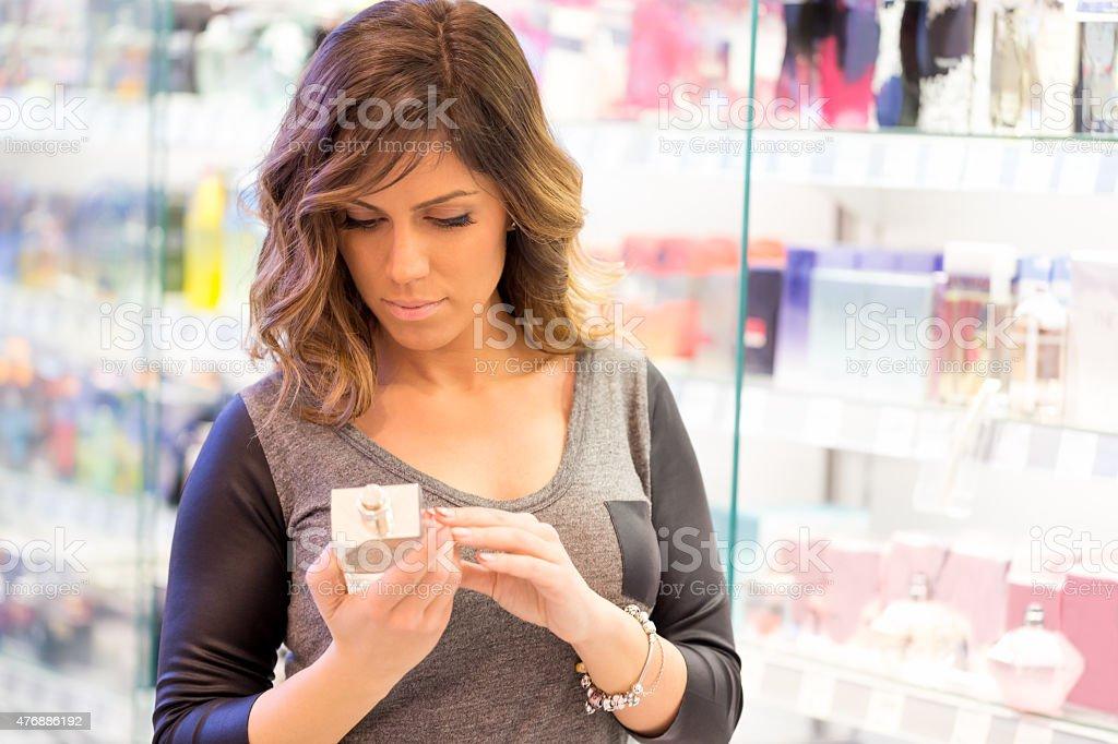 Women choosing perfume in mall stock photo
