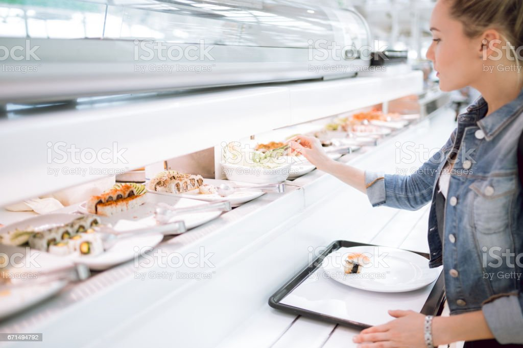 Women choosing sushi on the food court stock photo