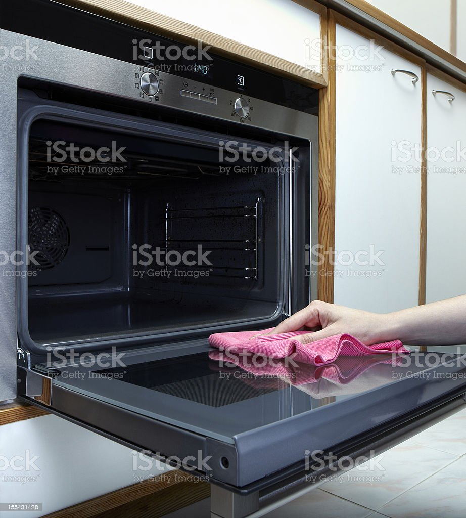 Women cleaning the oven with towel stock photo