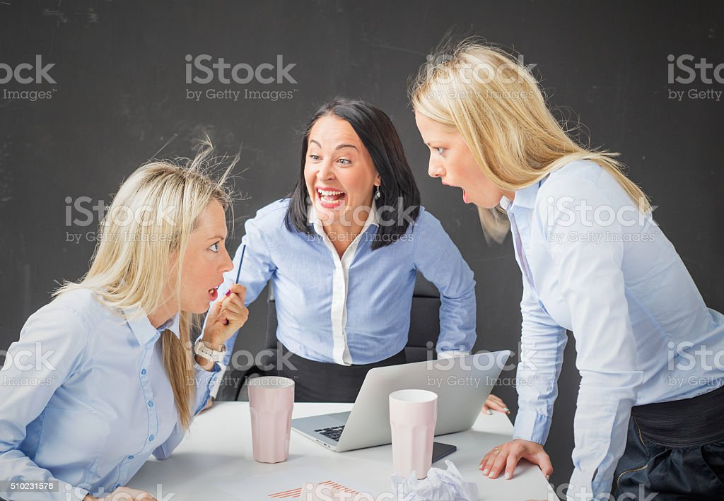 Women colleagues arguing and screaming in the office stock photo