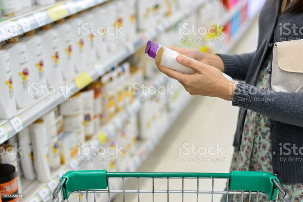 women comparing shampoo  in supermarket stock photo