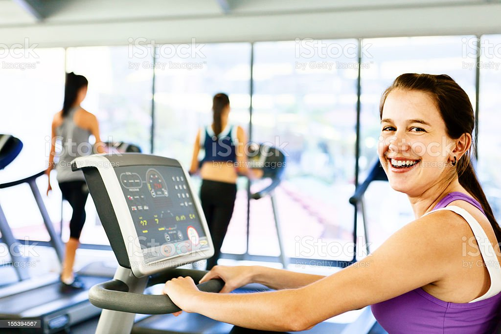 Women confidently using gym equipment and smiling stock photo