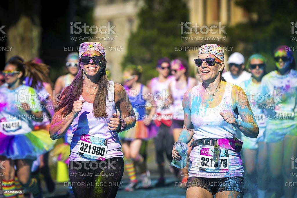 Women couple runs the Color Vibe 5K race stock photo