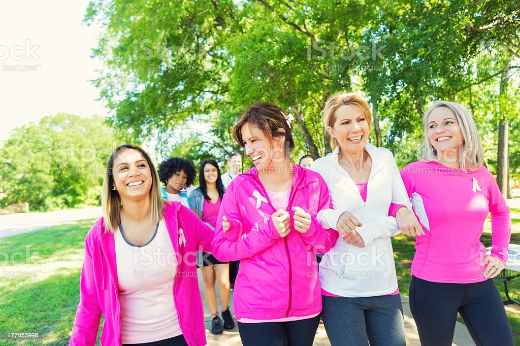 Women crossing finish line together in breast cancer awareness race stock photo