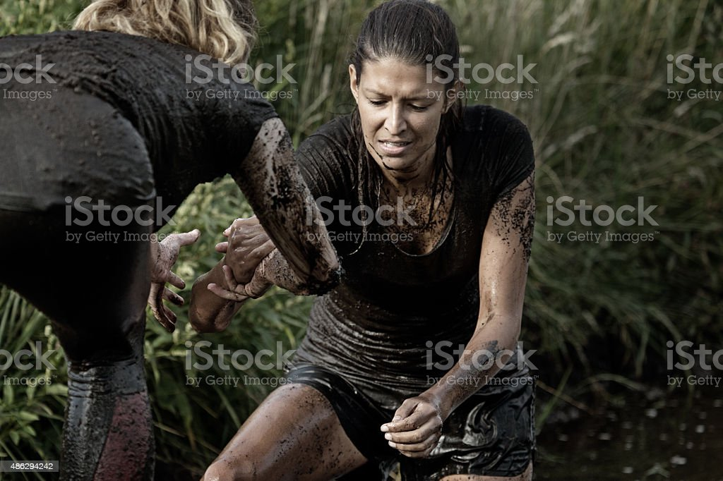 women crossing mud obstacle stock photo