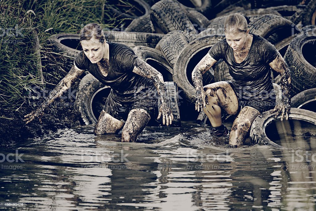 women crossing muddy canal with tires stock photo