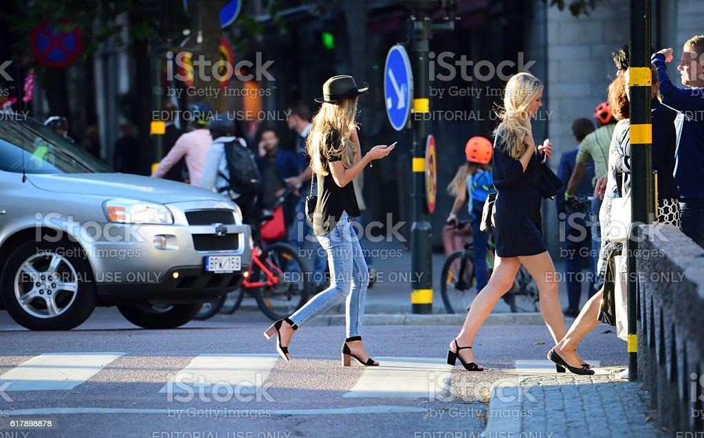 Women crossing street, zebra crossing, traffic in background stock photo
