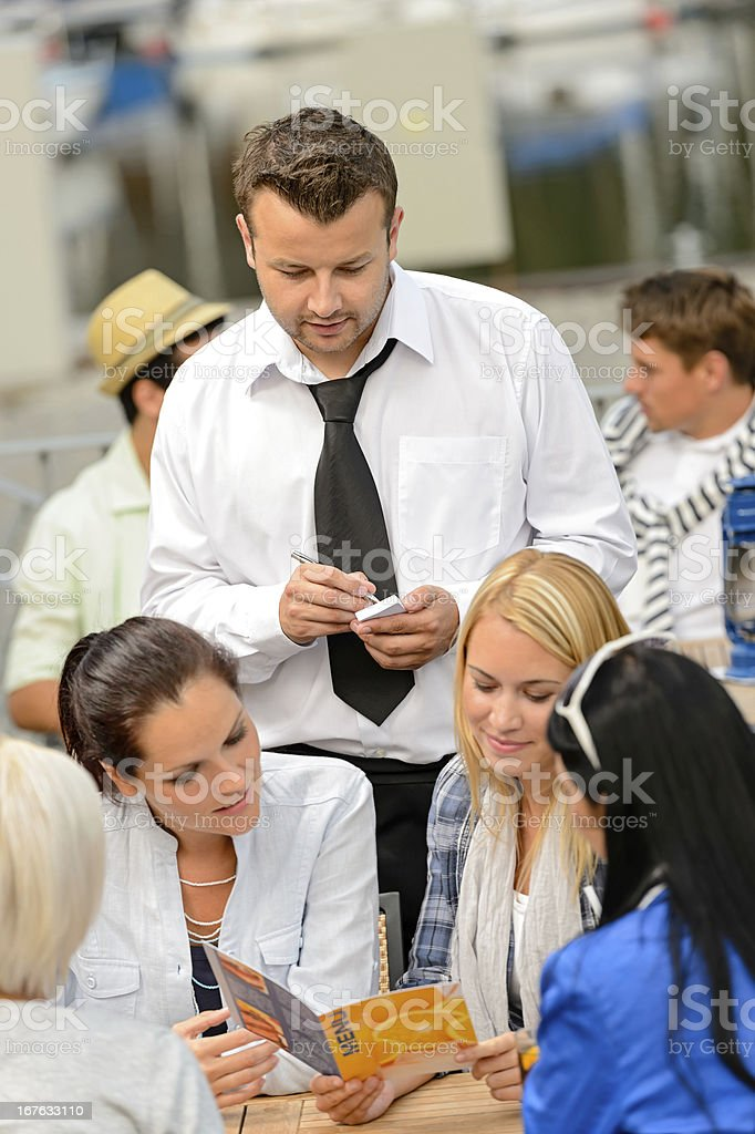 Women customers ordering from waiter at restaurant royalty-free stock photo