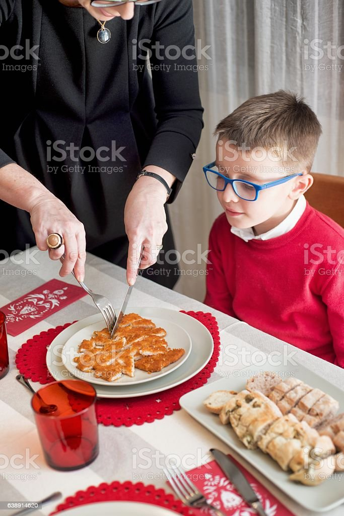 Women Cutting Cutlet to her Son stock photo