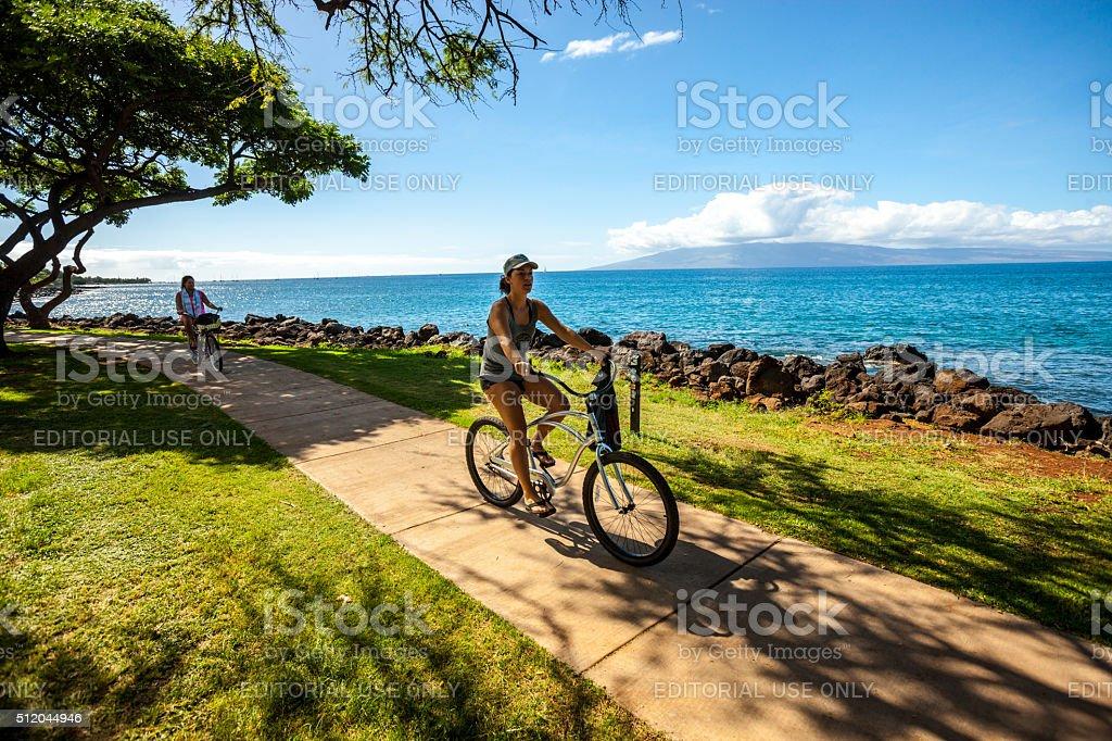 Women cycling along the beach, Maui stock photo