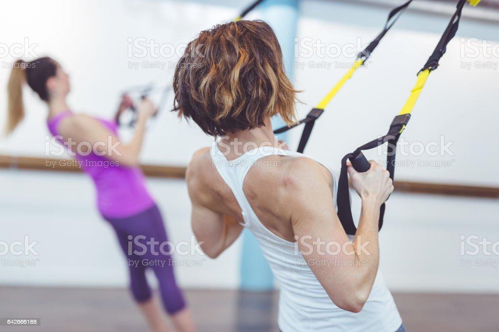 Women Doing Barre + TRX Workout stock photo