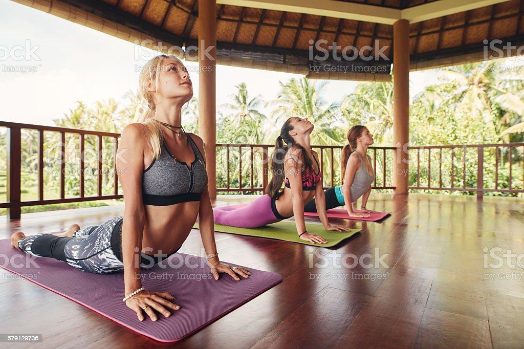 Women doing cobra pose at yoga class stock photo