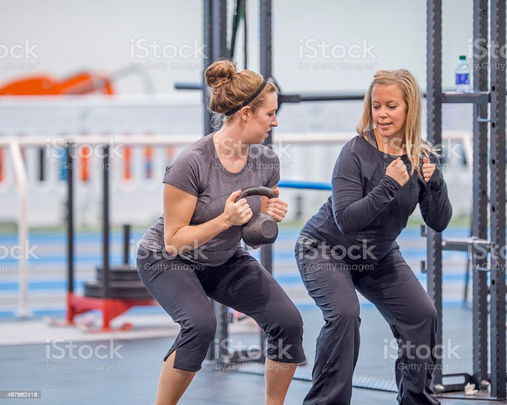 Women Doing Squats at the Gym stock photo