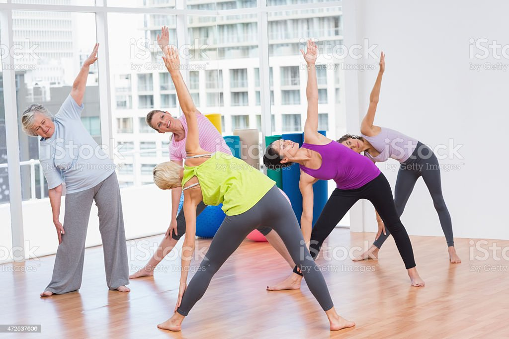 Women doing stretching exercise in gym stock photo